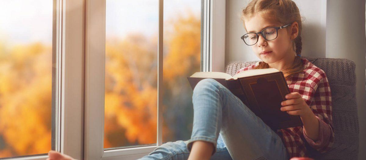 Girl reading in bay window